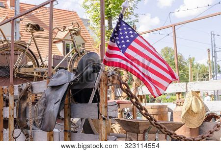American Flag On The Bodywork Of Vintage Ford Truck With Old Farm Stuff- Straw Hat,  Rusty Bike, Rus