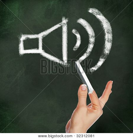 School blackboard and hand with chalk drawing sound symbol