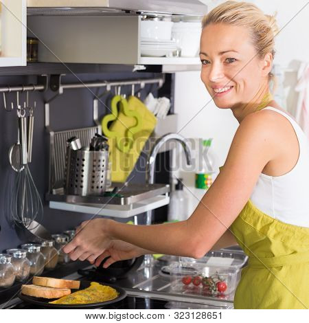 Young Mother Cooking Deliciousat Omlet At Home.
