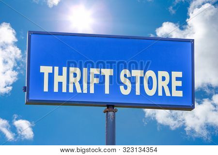 Thrift store sign against a blue sky with clouds and sunshine
