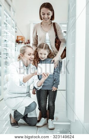 Mother And Daughter Looking At Druggist S Tablet Interestedly