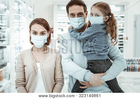 Family In The Drugstore Wearing A Medical Face Mask