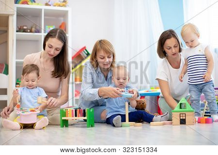 Babies With Adults Play In Creche Or Kindergarten