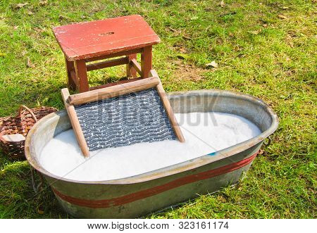 An Old Fashioned Washing Trough Filled With Water, A Vintage Washboard And Soap That Wash The Laundr