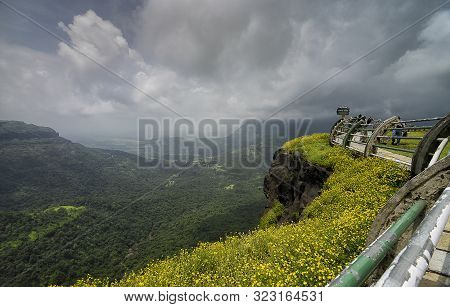 Maharashtra, India, September, 2013, Tourist At Malshej Ghat On A Cloudy Day With Yellow Flowers.