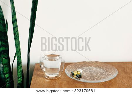 Omega 3, Spirulina, Chlorophyll,magnesium Capsules And Glass Of Water On Wooden Table. Morning Vitam