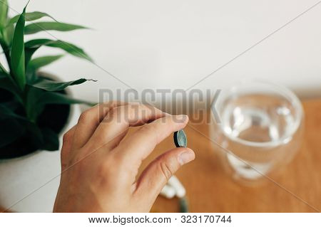 Hand Holding Chlorophyll Tablet Above Glass Of Water On Wooden Table. Morning Vitamin Nutrient Pill.
