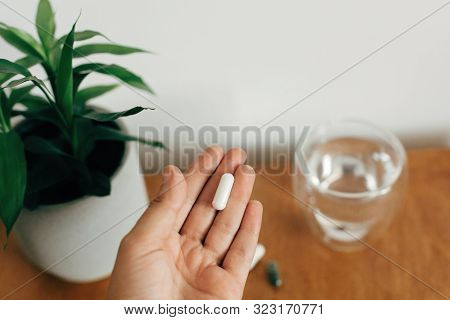 Hand Holding Magnesium Capsule Above Glass Of Water On Wooden Table. White Pill. Dietary Supplements