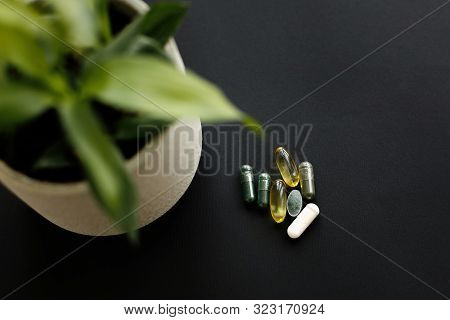 Dietary Supplements. Omega 3, Spirulina, Chlorophyll,magnesium  Capsules And Plant On Black Dark Bac