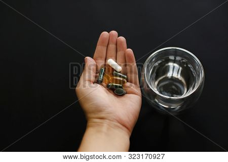 Dietary Supplements. Hand Holding Omega 3, Spirulina, Chlorophyll,magnesium  Capsules Above Glass Of