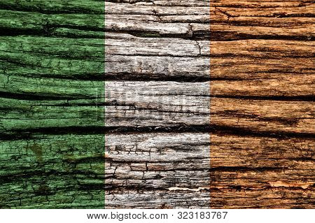 Ireland Flag On An Old Decrepit Wooden Surface. Textured Background For Creativity And Design.