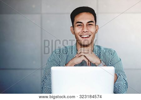 Happy Young Asian Businessman Working On Computer Laptop In His Workplace. Hands On Chin, Smiling An