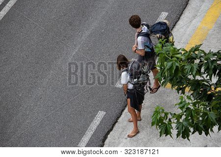 Santiago De Compostela, Spain; September 19, 2019: Couple Hitchhiking To Finisterre, Spain. Hitching
