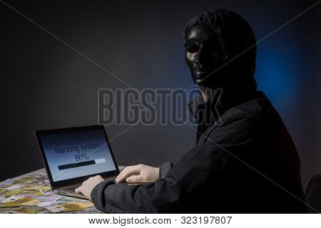 Anonymous hacker programmer uses a laptop to hack the system in the dark. The concept of cybercrime and hacking database. Money is scattered on the table. Focus on laptop poster