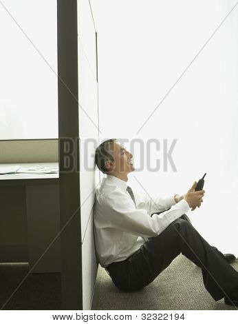 Asian businessman sitting against cubicle wall with telephone