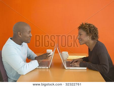African couple using laptops at table