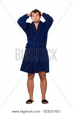 Full Length Portrait Of Tardy Young Man Wears Blue Bathrobe Holding Hands To Head, Unable To Wake Up