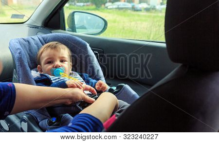 Children Car Chair. Baby Car Seat For Safety. Young Boy In The Child Seat And His Mother, Safe Drivi
