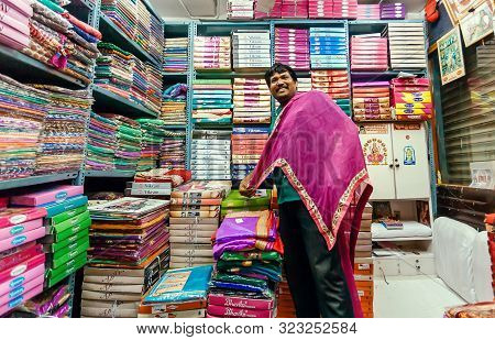 Bangalore, India - Feb 12: Trader Working With Female Fashion, Colorful Scarfs And Traditional Sari