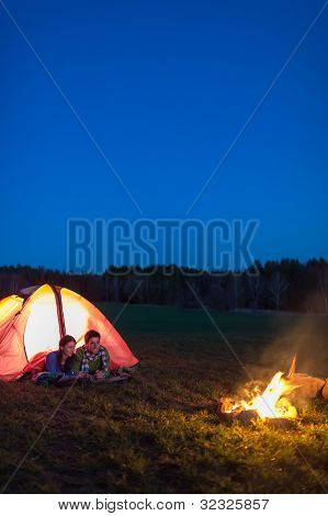 Romantic camping night couple lying in front tent by campfire
