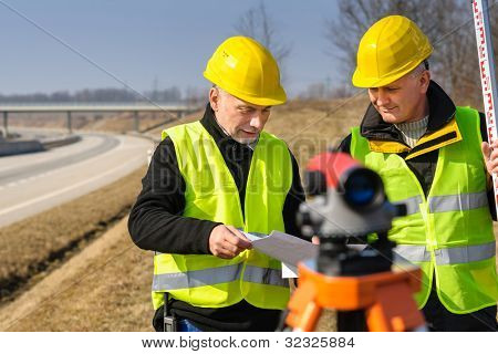 Two male geodesist with tacheometer checking plans standing by highway