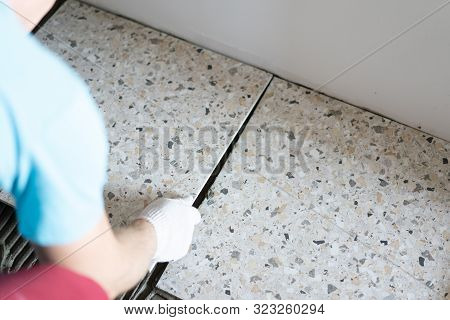 Repair And Decoration Of Apartments And Houses. Professionals Lay Porcelain Tiles On The Floor In Th