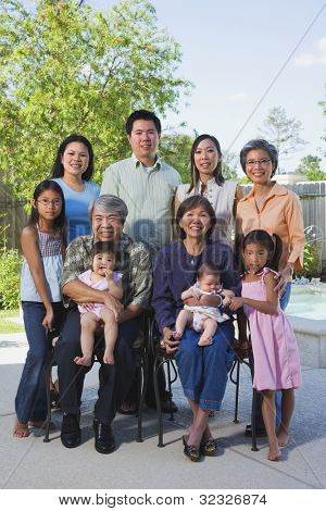 Multi-generational Asian family smiling outdoors
