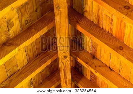 Closeup Of Center Support Beam And Rafters Of Roof Of Picnic Shelter In Local Park.