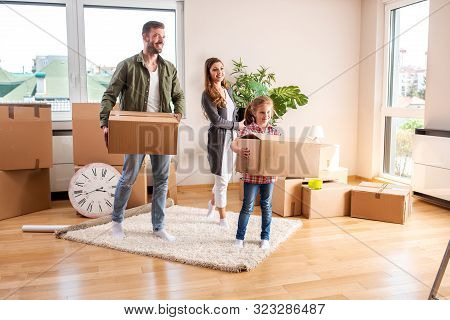 Happy Couple And Their Daughter Moving In A New Apartment