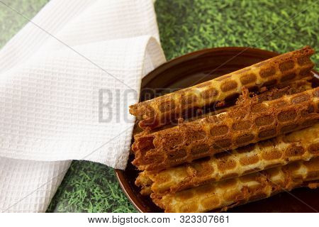 Homemade Wafer Rolls Lie On A Brown Plate On The Grass. Next To A Snow-white Napkin. Dessert On Natu