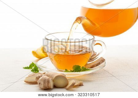 Ginger Tea In A Cup. Hot Drink With Lemon, Ginger And Mint On White Background. Tea Is Poured From A