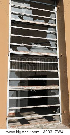 Large Window With Glass Completely Broken By Vandals And Iron Bars