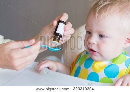 Vitamins For Young Children. Mom Drips Vitamins Into A Spoon While Feeding Her Little Son. Healthy C