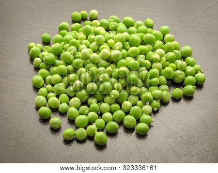 Green Pea Pod Closeup Peas. Closeup Of Fresh Green Peas (pisum Sativum) In A Glass Jar On A Wooden T