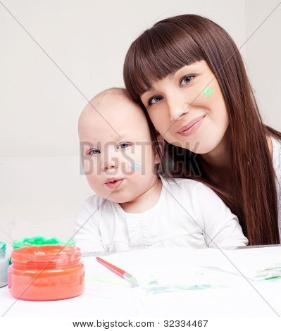 happy mother and daughter painting at home