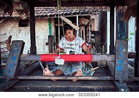 Bali, Indonesia - Sep 21, 2019: Weaver Young Woman Behind A Loom, Handmade Manufacturing Fabric And