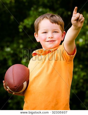 Child with football celebrating by showing that he's Number 1
