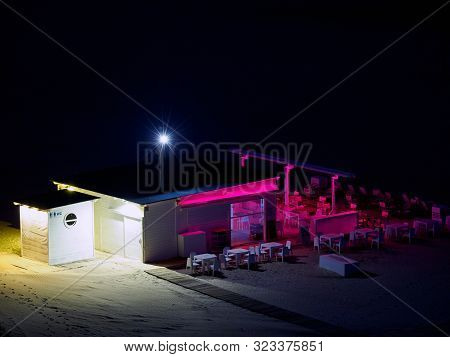 Night Photo Of A Bar On A Mediterranean Beach, With Red And White Lighting, On A Closed Night