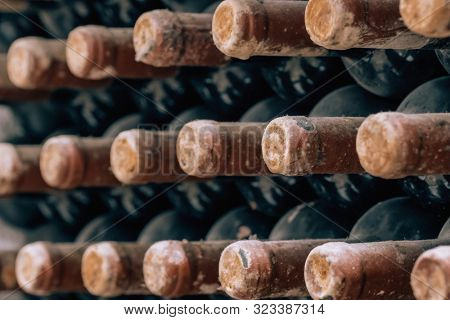 Wine bottles stacked up in old wine cellar close-up background. Underground wine cellars in Moldova