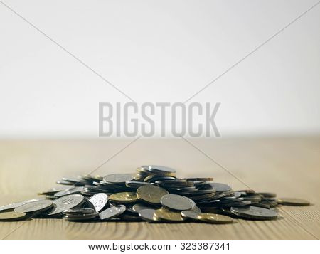 heap of coins on the wooden table