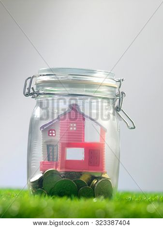 morning scene of model house and coins in glass jaron top of grass