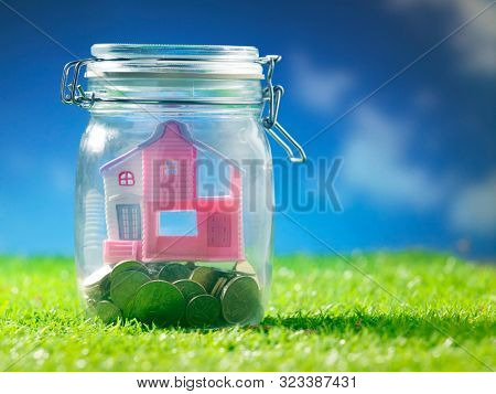 afternoon with ble sky ,model house and coins in glass jar on the grass