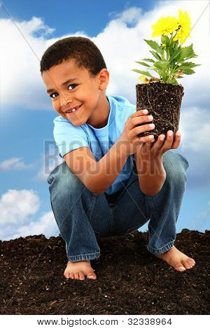 Adorable  Black Boy Child Planting Flowers for Earth Day Barefoot in Soil Holding Flower