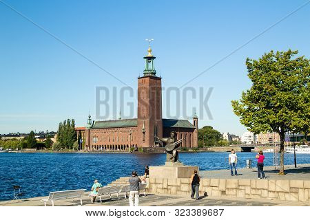 Sweden, Stockholm - Circa Aug 2013: Evert Taube Monument On Background Of Stockholm City Hall. Touri