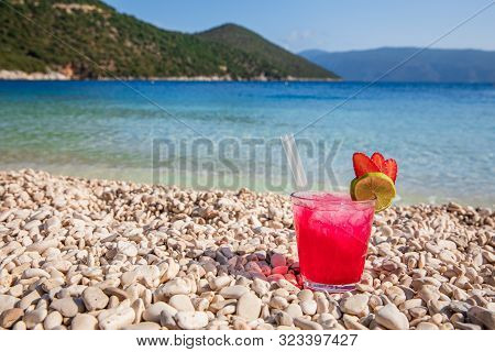 Glass Of Cold Strawberry-daiquiri Cocktail On The Backgrond Of Antisamos Beach, Kefalonia Island, Gr