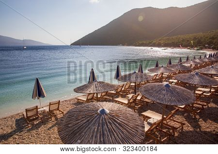 Summer Sunny Morning Sunbeds And Umbrellas Of Antisamos Beach On The Kefalonia Island, Ionian Sea, G