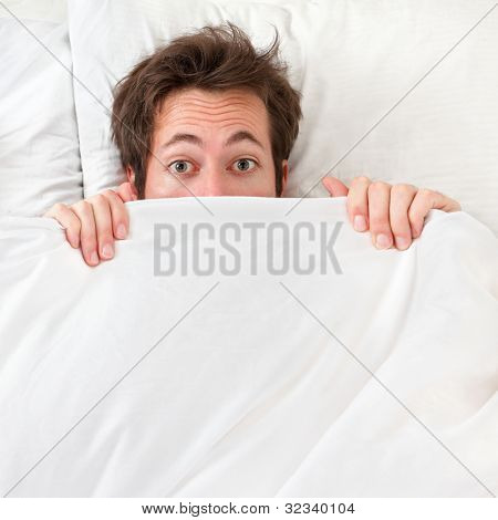 Scared man hiding in bed under the sheets. Funny concept image with young caucasian male model home in bed.
