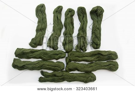 10 hanks of green linen yarn isolated on a light background.  Crafting supplies in an olive green or khaki green skeins. poster