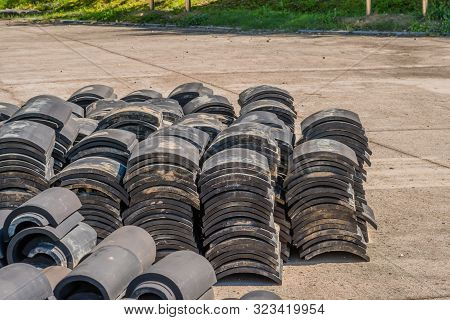 Stacks Of Black Ceramic Roofing Tiles Sitting On Concrete With Lawn Of Public Park In Background.