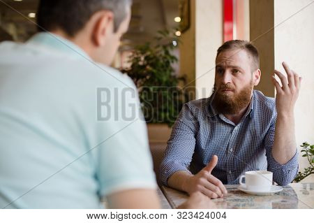 Two Men Discussing Difficult Issues With Emotions During Coffee Break In Cafe Talking About Problems